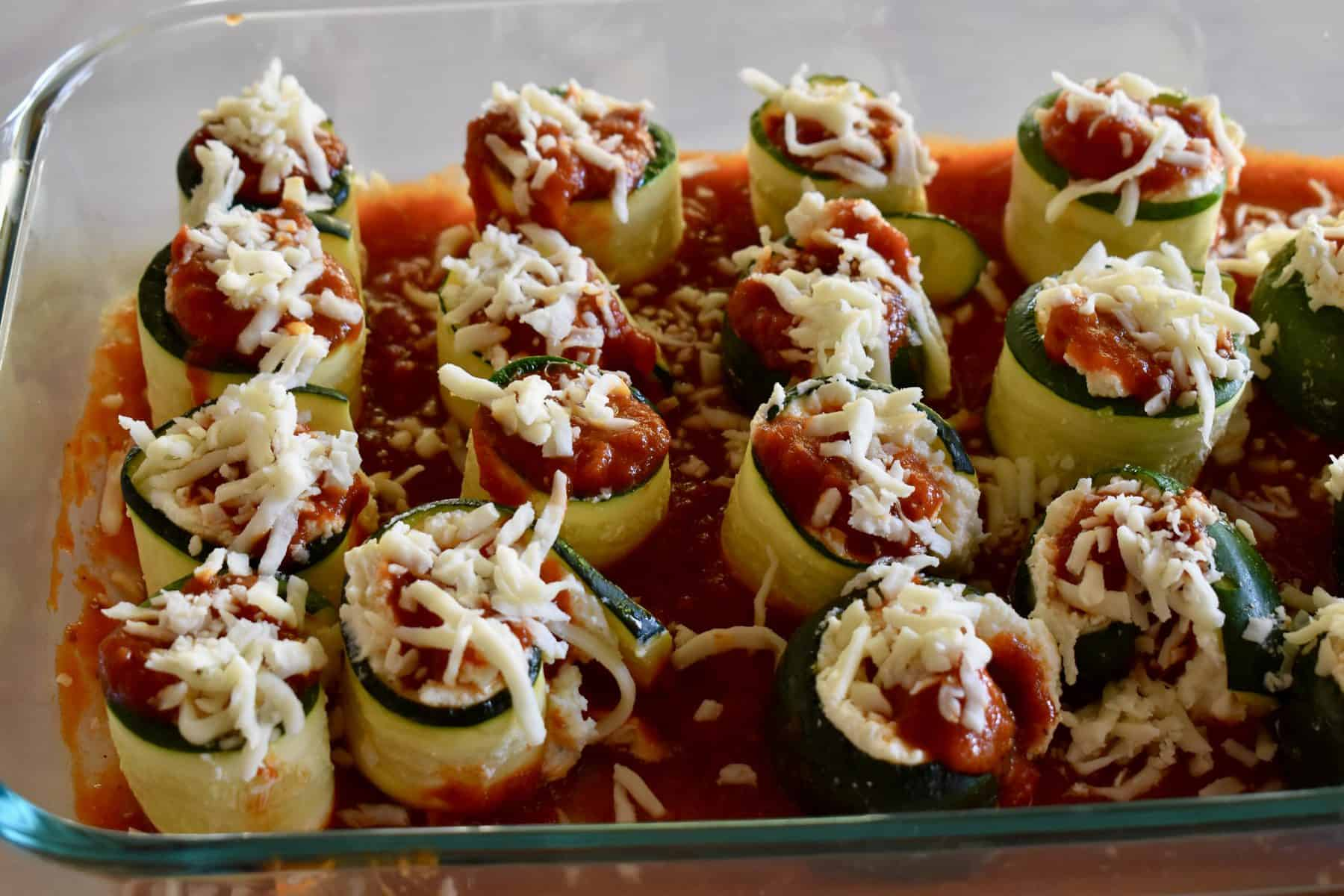 Zucchini rolls ups in a pan of marinara sauce.
