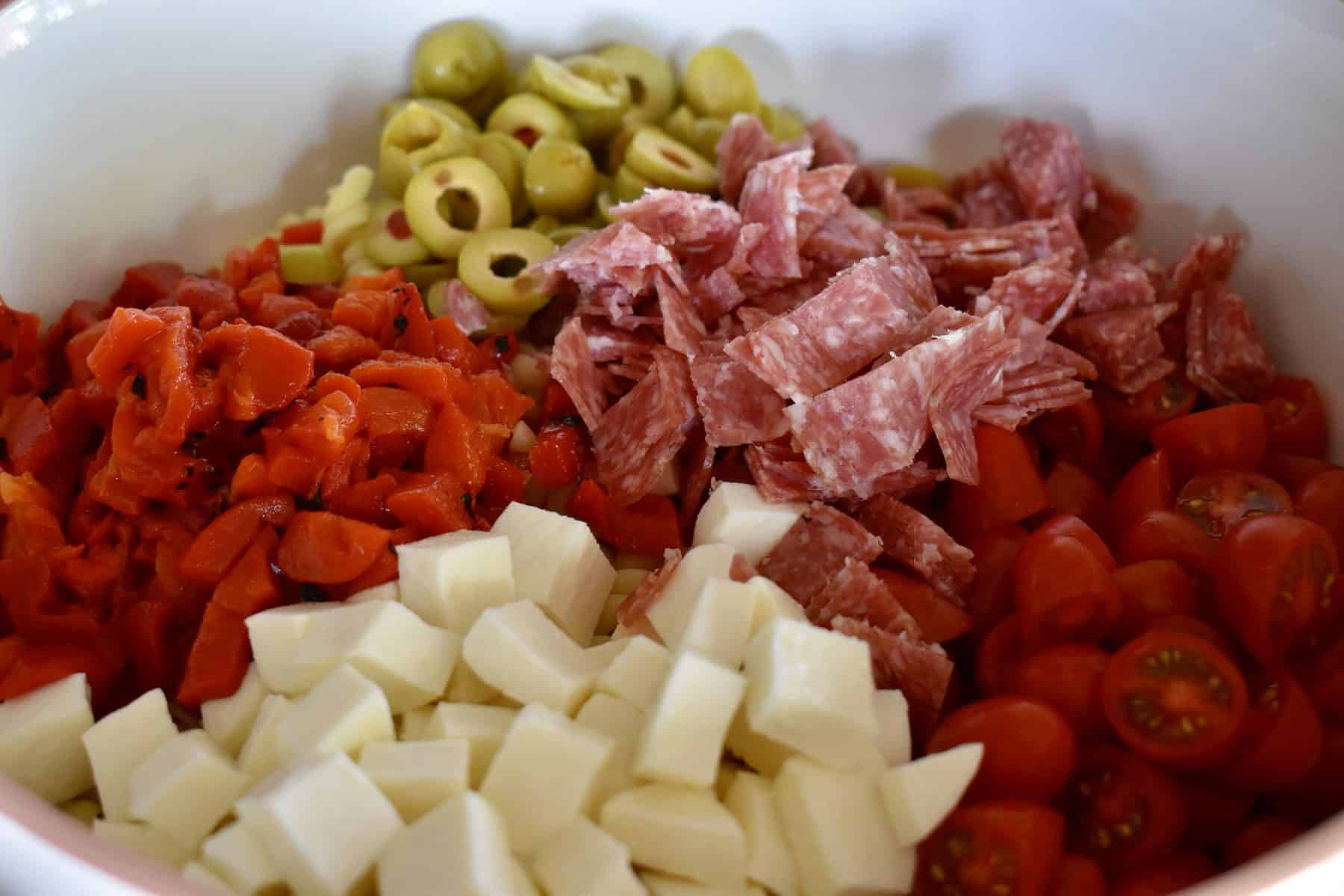 Close up view of the pasta salad with cherry tomatoes, mozzarella, bell peppers, green olives, and salami.
