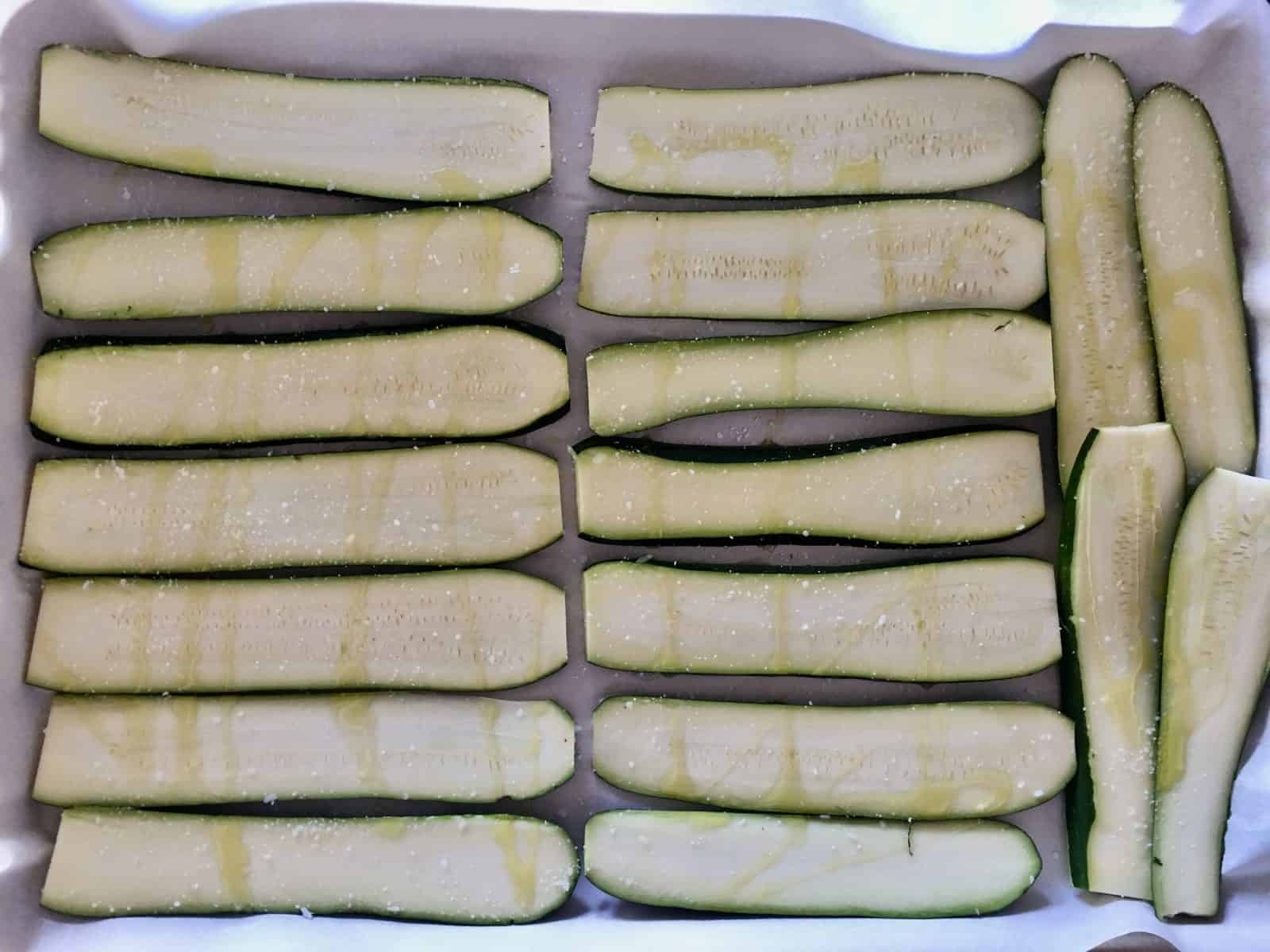Sliced Zucchini on parchment paper on a baking sheet.