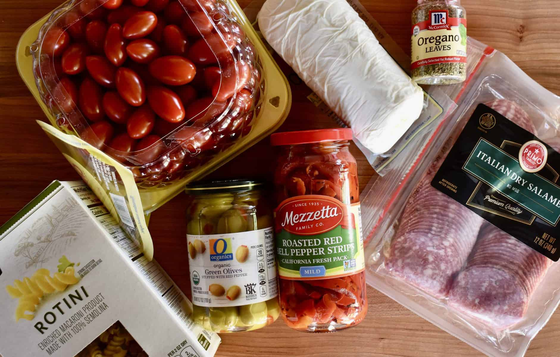 Overhead photo of wood cutting board with rotini, salami, tomatoes, mozzarella, green olives, roasted red peppers, and oregano.