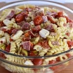 Rotini pasta in a clear bowl with toppings and dressings tossed in it.