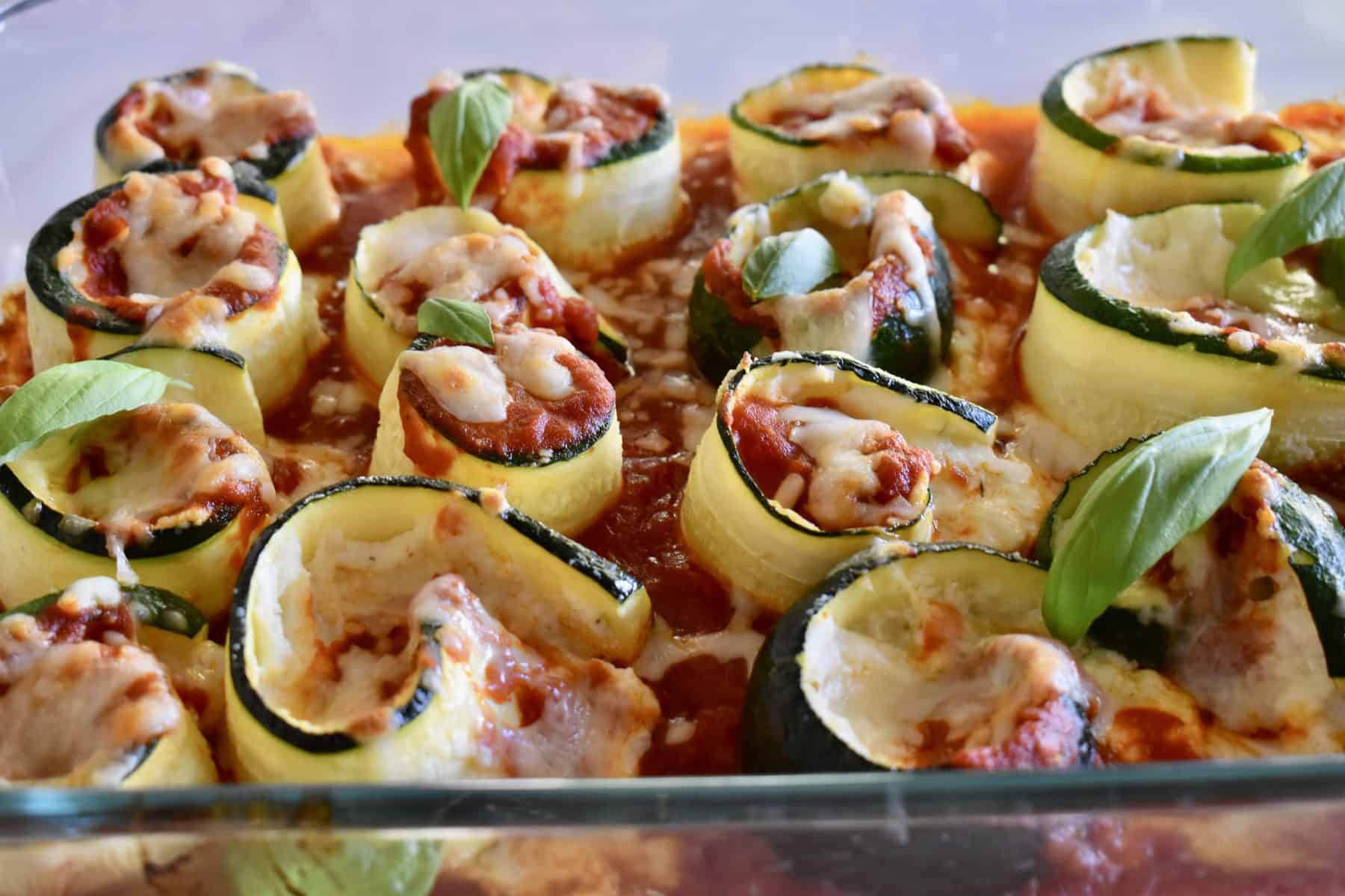 Zucchini Ricotta Roll Ups in a glass pan with basil leaves on top.