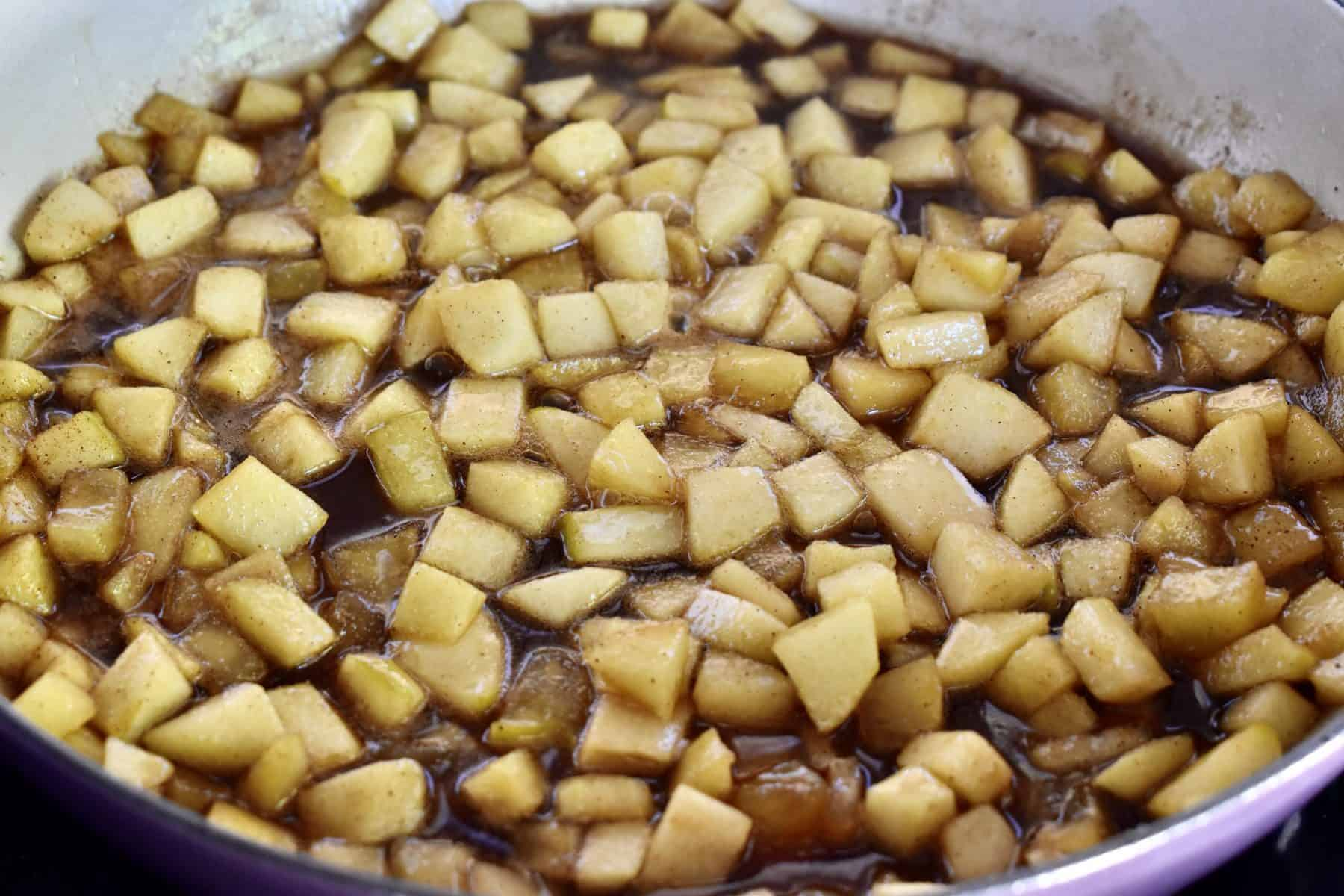 cinnamon apples in a skillet with brown sugar and cinnamon.