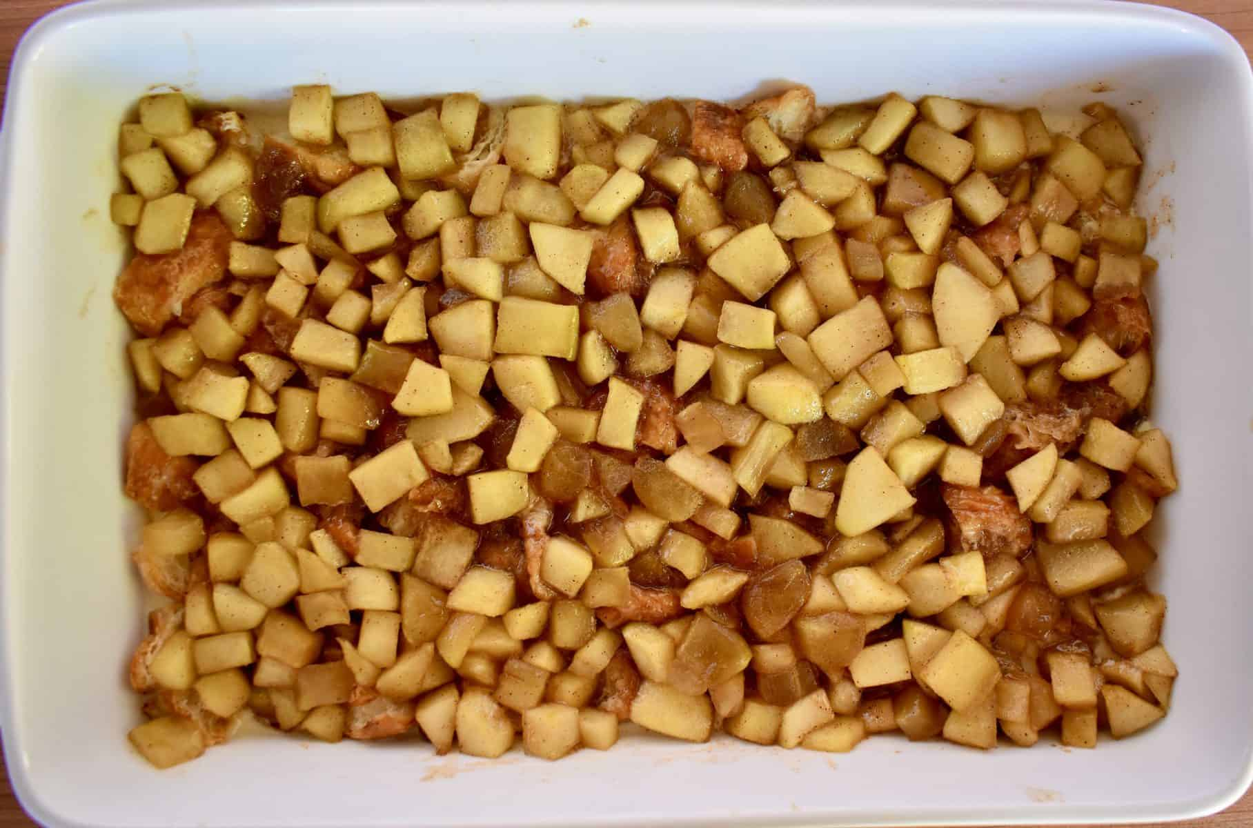 overhead photo of croissant baked French toast with cinnamon apples on top.