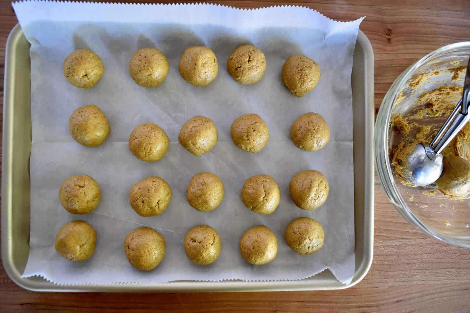 overhead photo of pumpkin spice truffle batter rolled into balls on a lined cookie sheet.