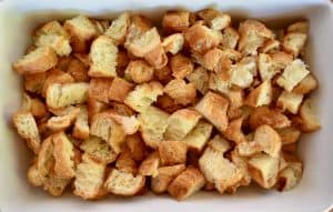 large chunks of croissant in a white baking dish.