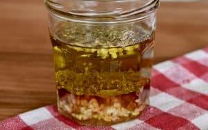 Italian dressing mixture in a glass jar on a wooden cutting board.