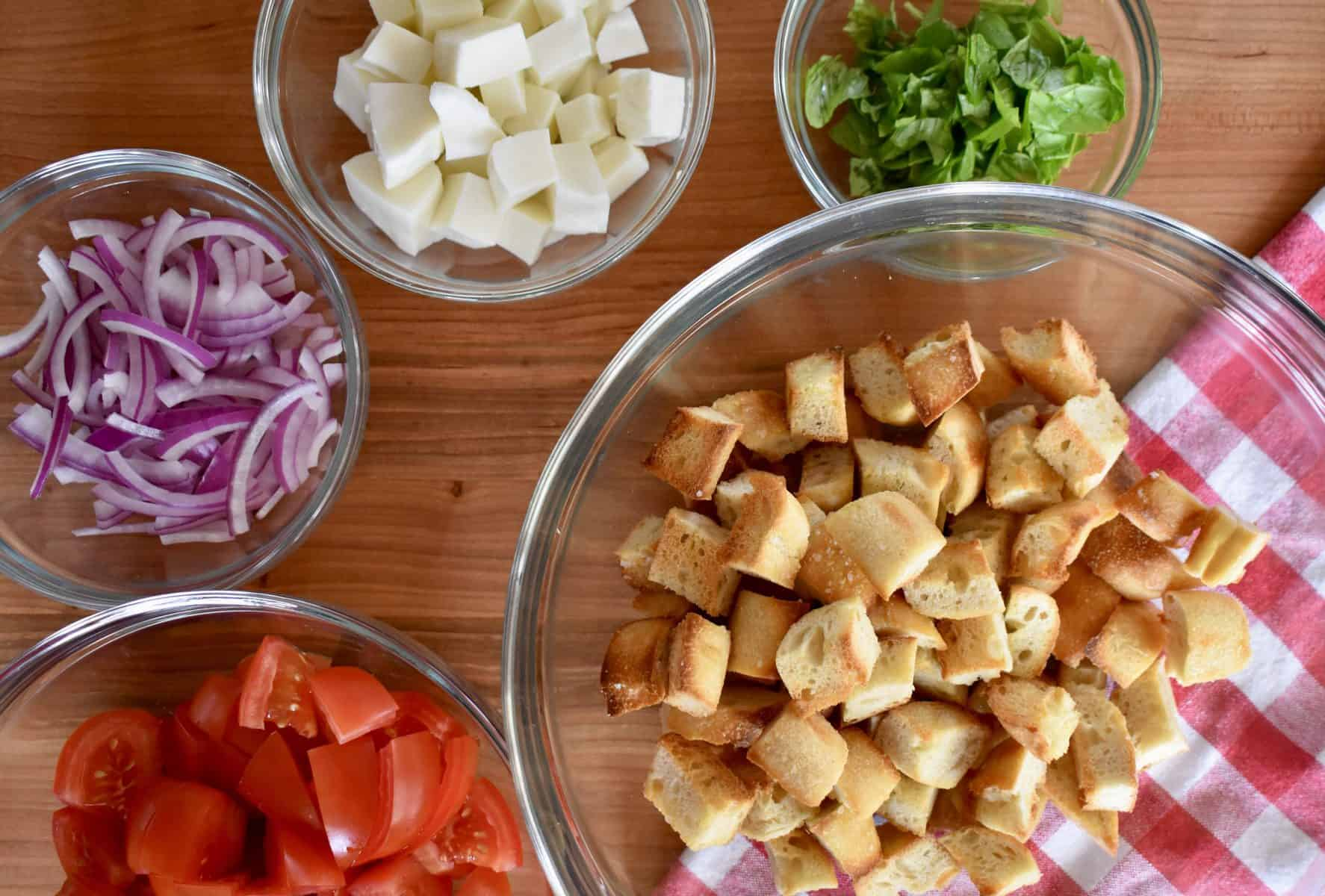 Overhead photo of bread cubes, tomatoes, mozzarella, sliced onions, and basil.
