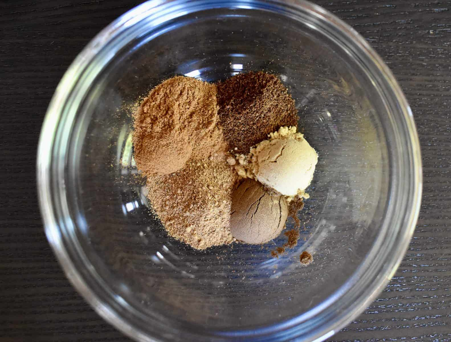overhead photo of nutmeg, cinnamon, ginger, cloves, and allspice in a glass bowl.