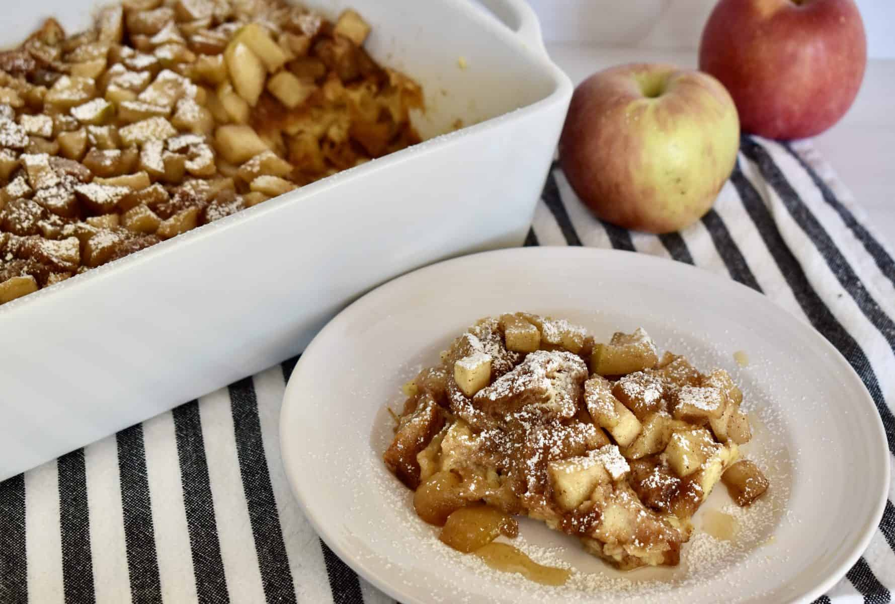 Croissant Baked French Toast in a dish with apples behind it.