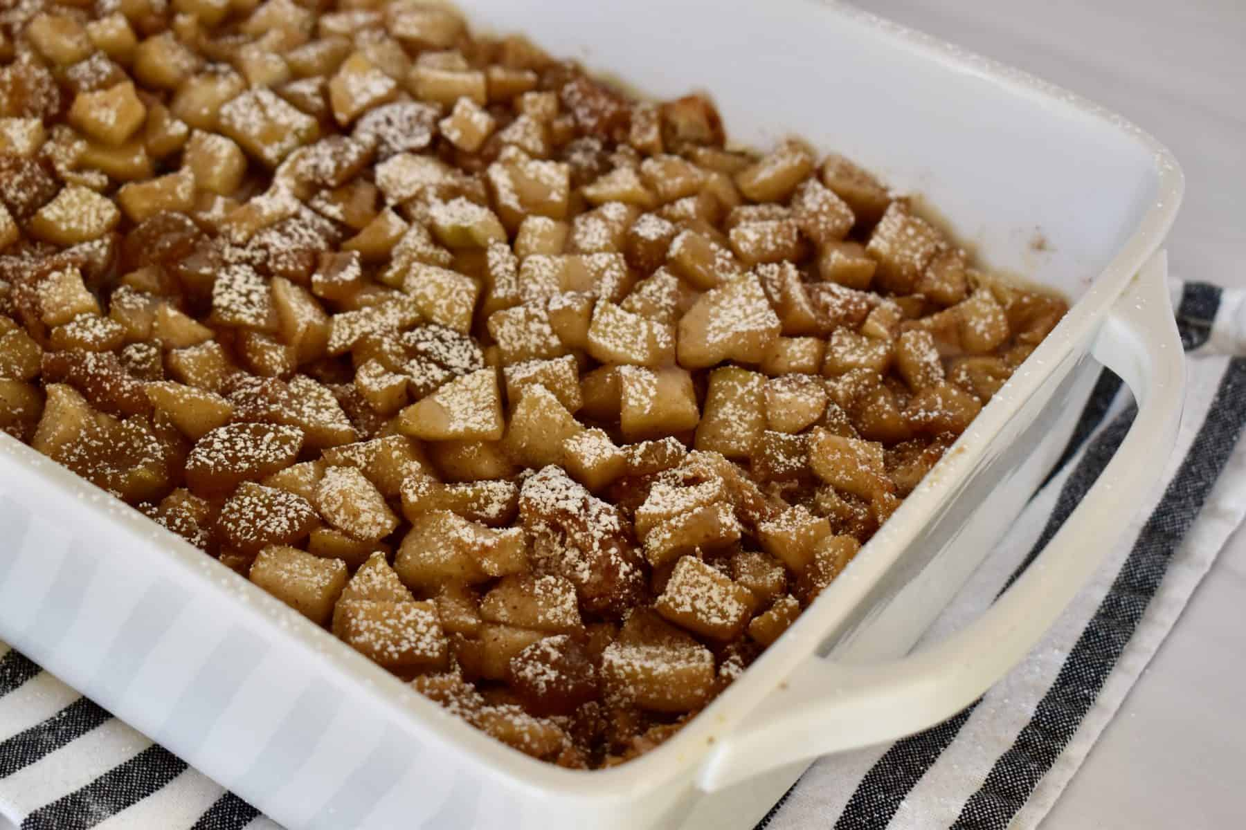 Croissant baked French toast with cinnamon apples in a white baking dish with powdered sugar on top.