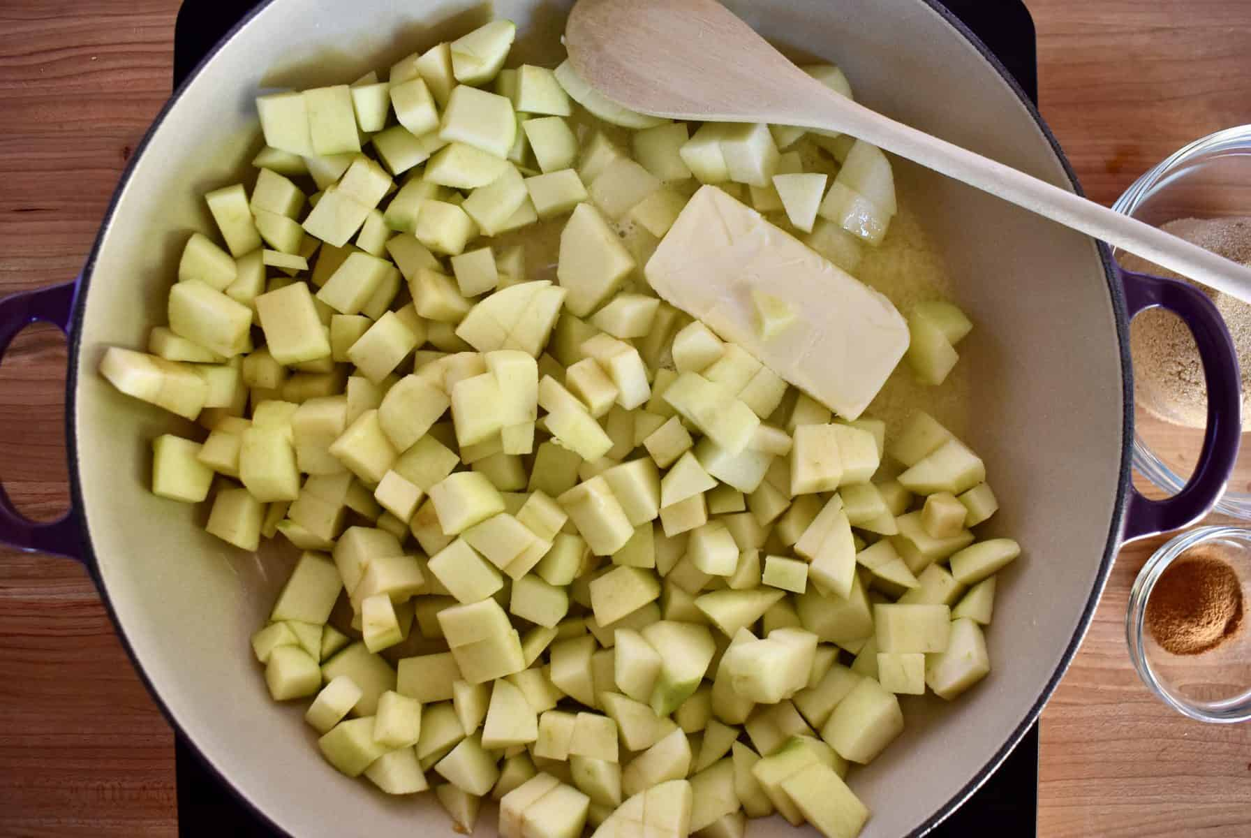 apples in a skillet with a stick of butter and a wooden spoon.