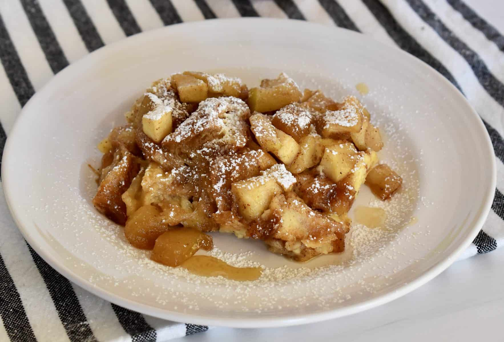 White plate with croissant baked French toast and cinnamon apples with powdered sugar sprinkled overtop.