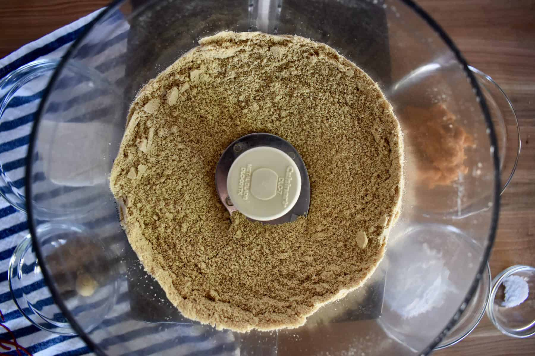 overhead photo of graham cracker crumbs in a food processor.