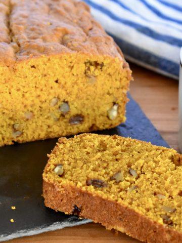 Pumpkin Walnut Raisin Bread on a cutting board with a cup of coffee.