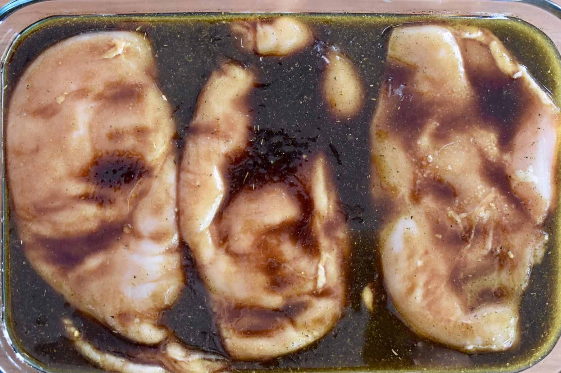 overhead photo of marinade poured over the chicken breasts.