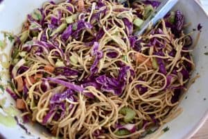 Overhead photo of asian noodle salad in a large bowl with tongs in it.