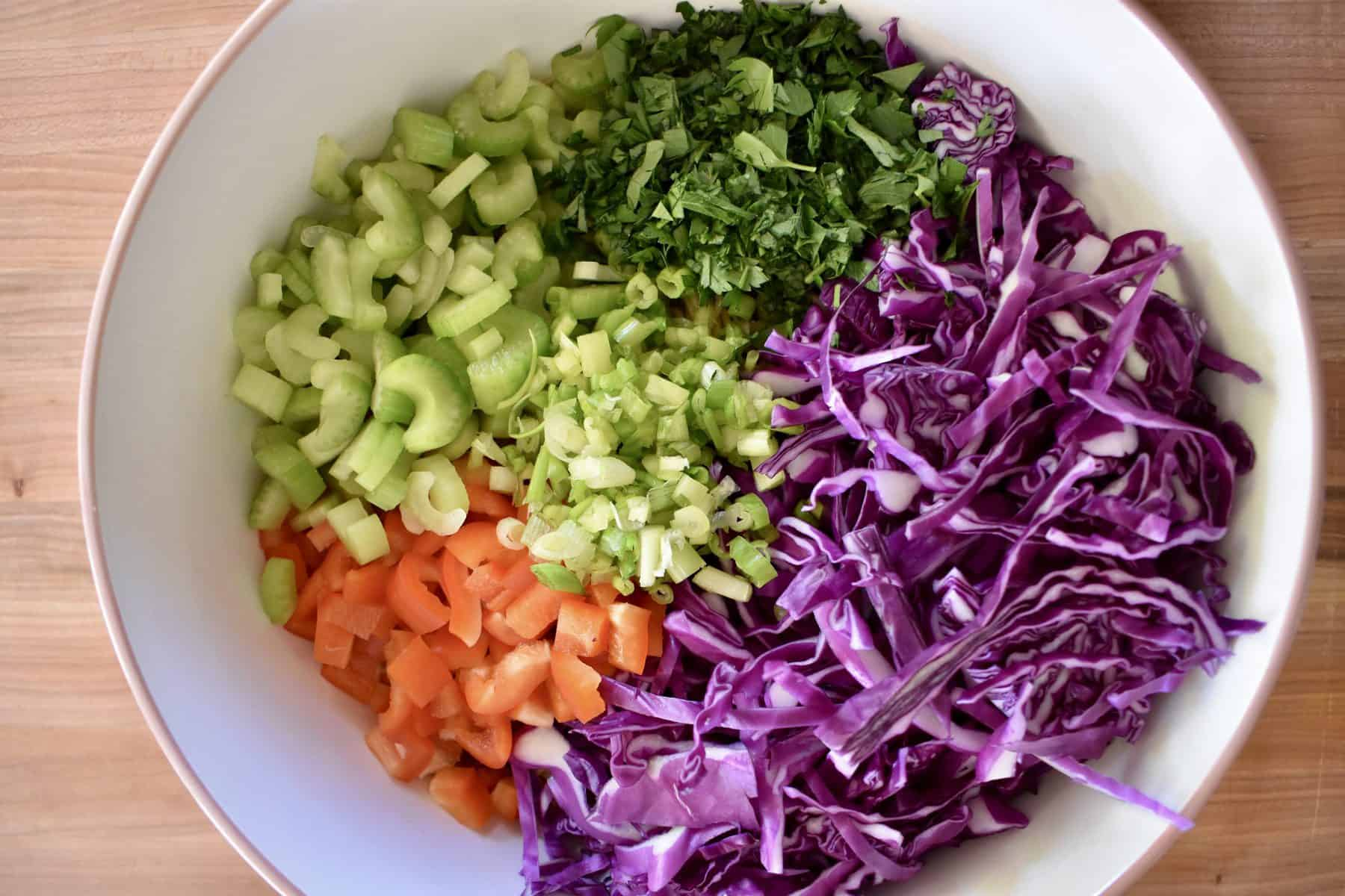 overhead photo of cabbage, celery, bell peppers, green onion, and whole wheat noodles in a large mixing bowl.