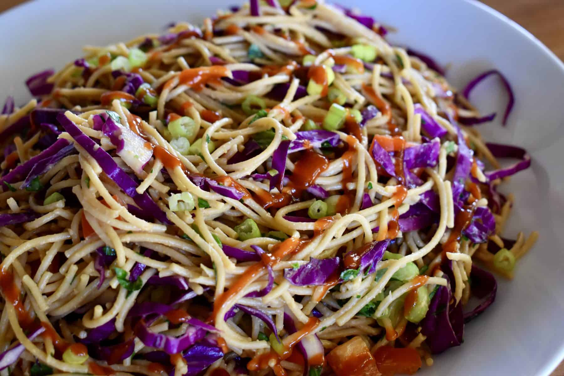Asian noodle salad in a white bowl with siracha drizzled on top.