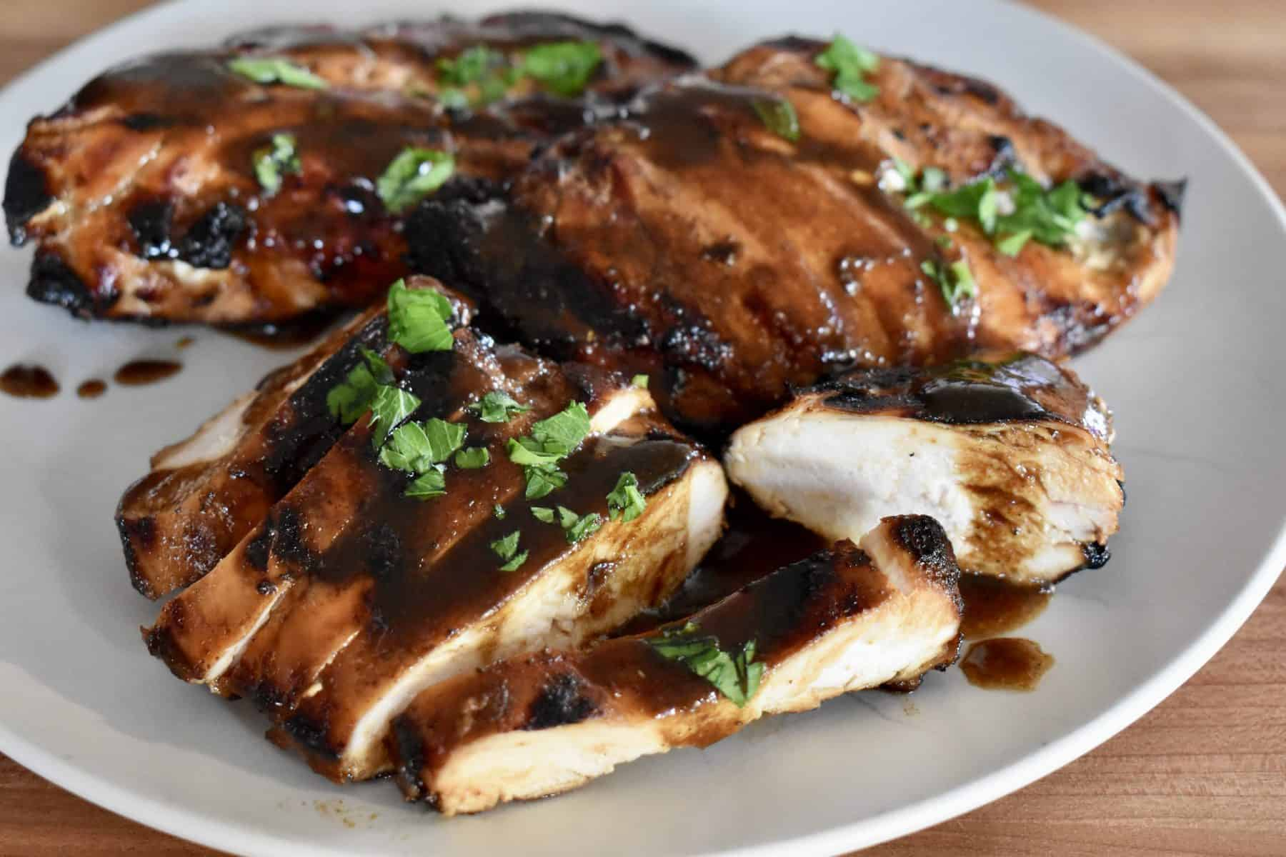 Grilled Marinated Chicken with Balsamic sauce on a white plate.
