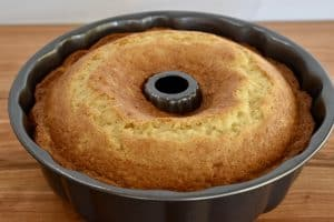 cooked pineapple cake in the Bundt Cake pan on a wooden surface.