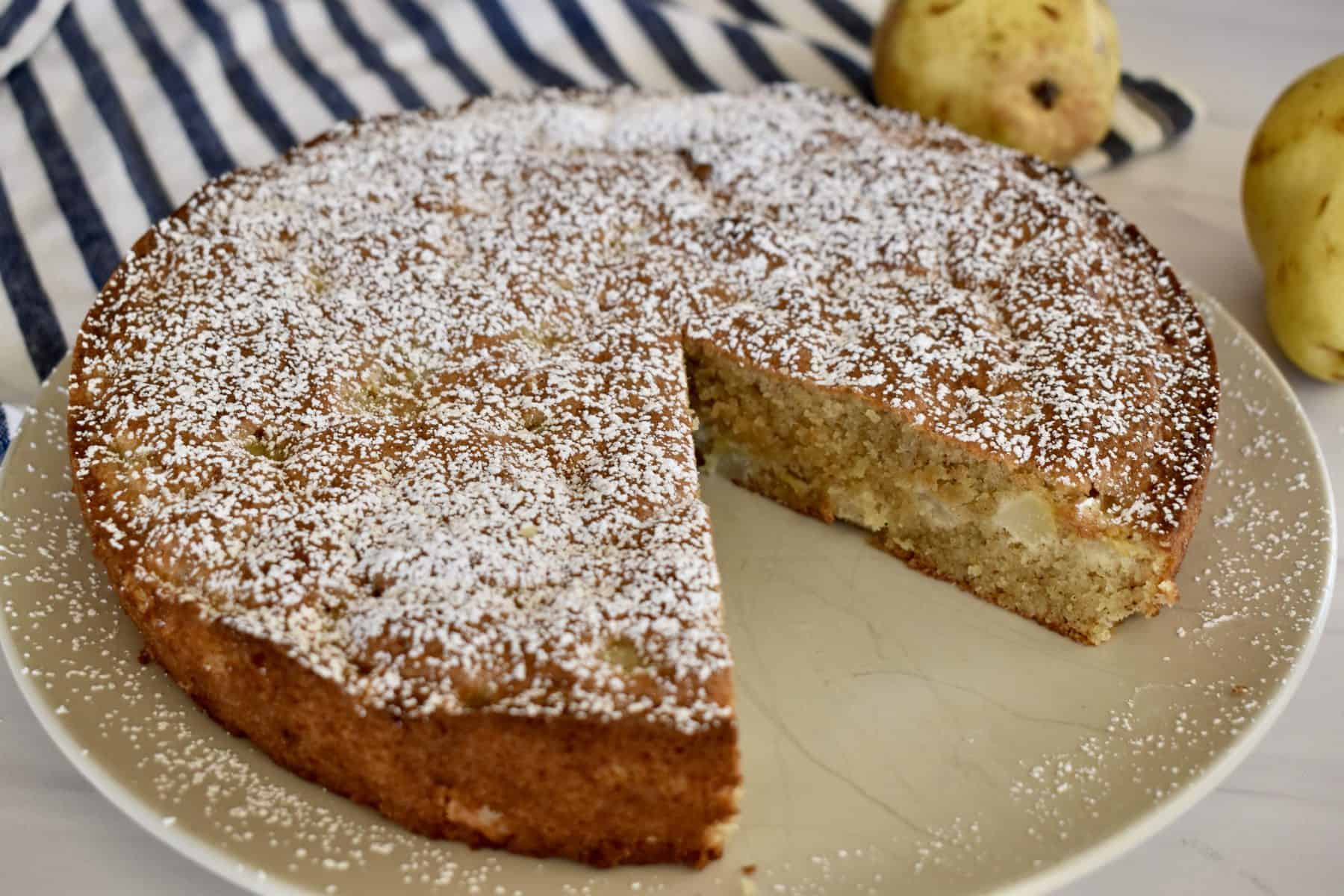 Almond Flour Pear Cake on a plate with a slice cut out of it.