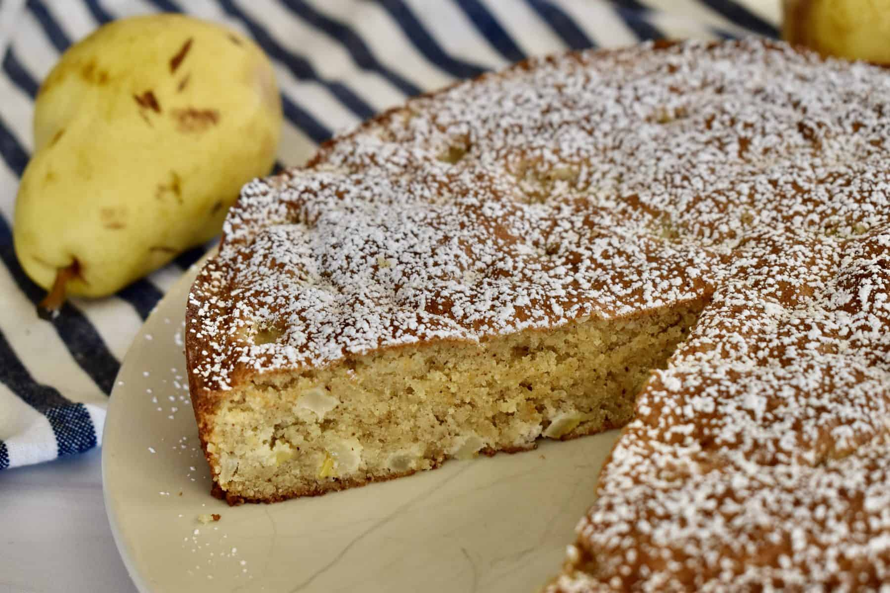 Almond Flour Pear Cake on a plate with pear in the background.