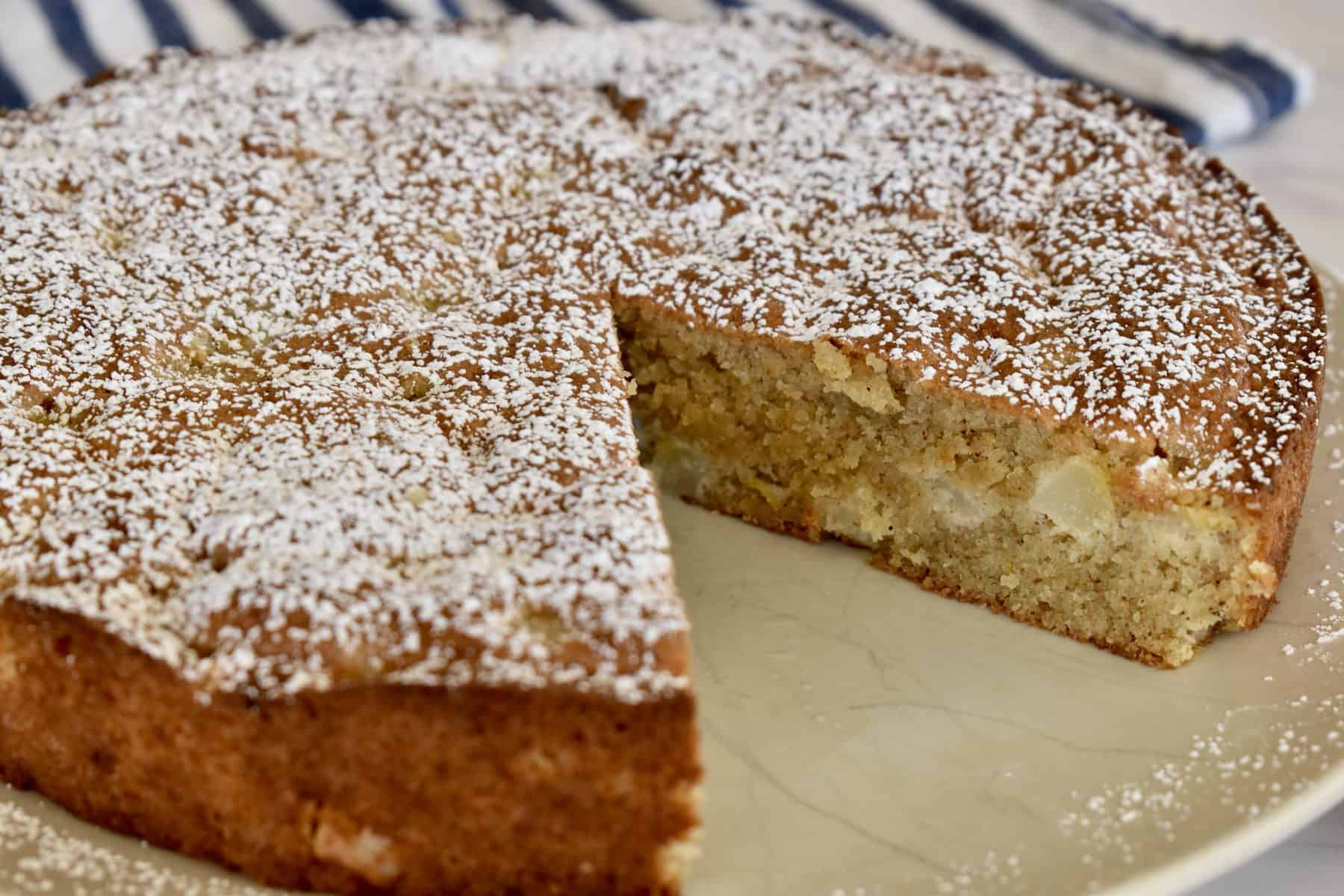 Almond Flour Pear Cake on a plate with a slice taken out of it.